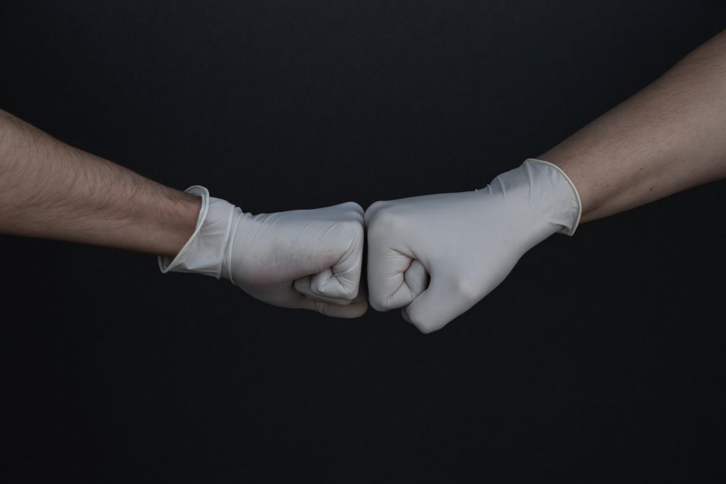 Photo of two hands in latex gloves pounding each other