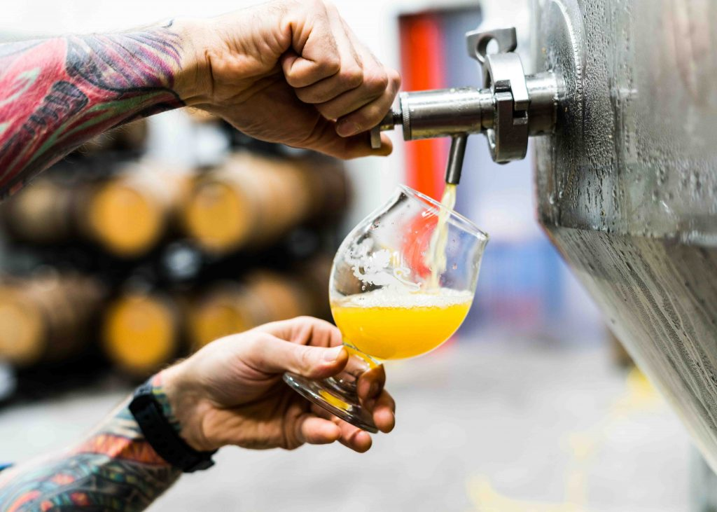 Photo of a hand filling a glass of beer from an industrial beer tank