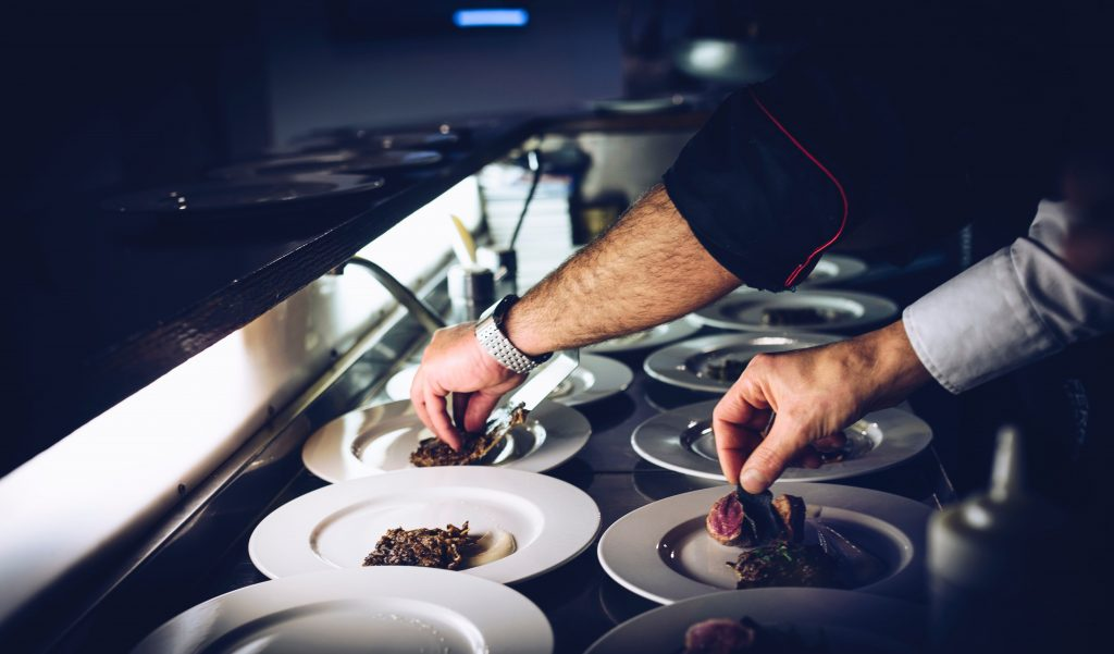 Photo of hands plating dishes in a chef's kitchen
