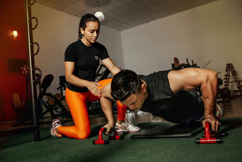 photo of a personal trainer helping her client do a pushup