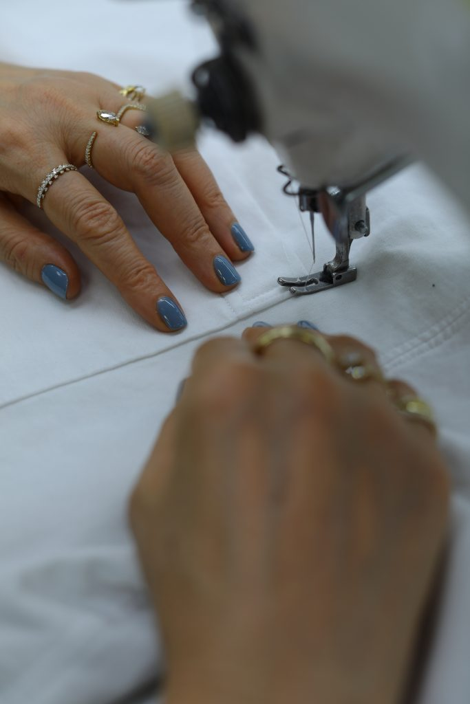 photo of hands sewing fabric with a sewing machine