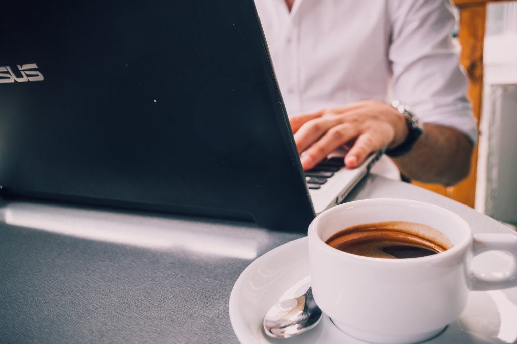 Person typing at a laptop with an espresso