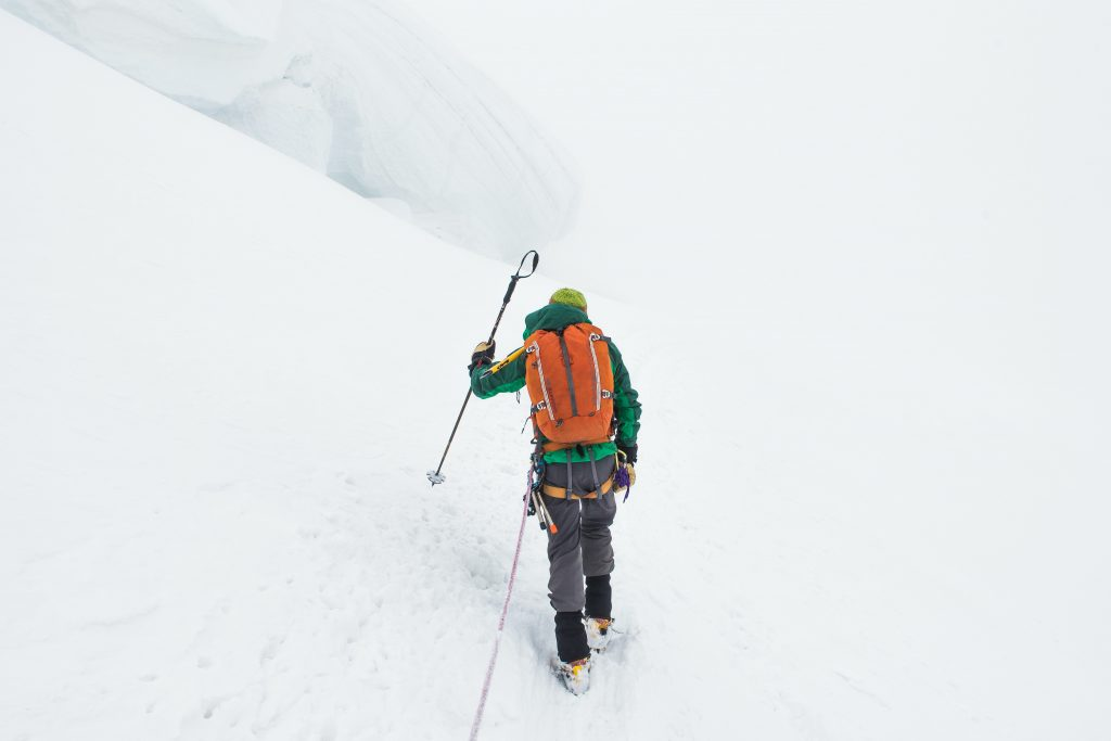 person walking up a snowy mountain