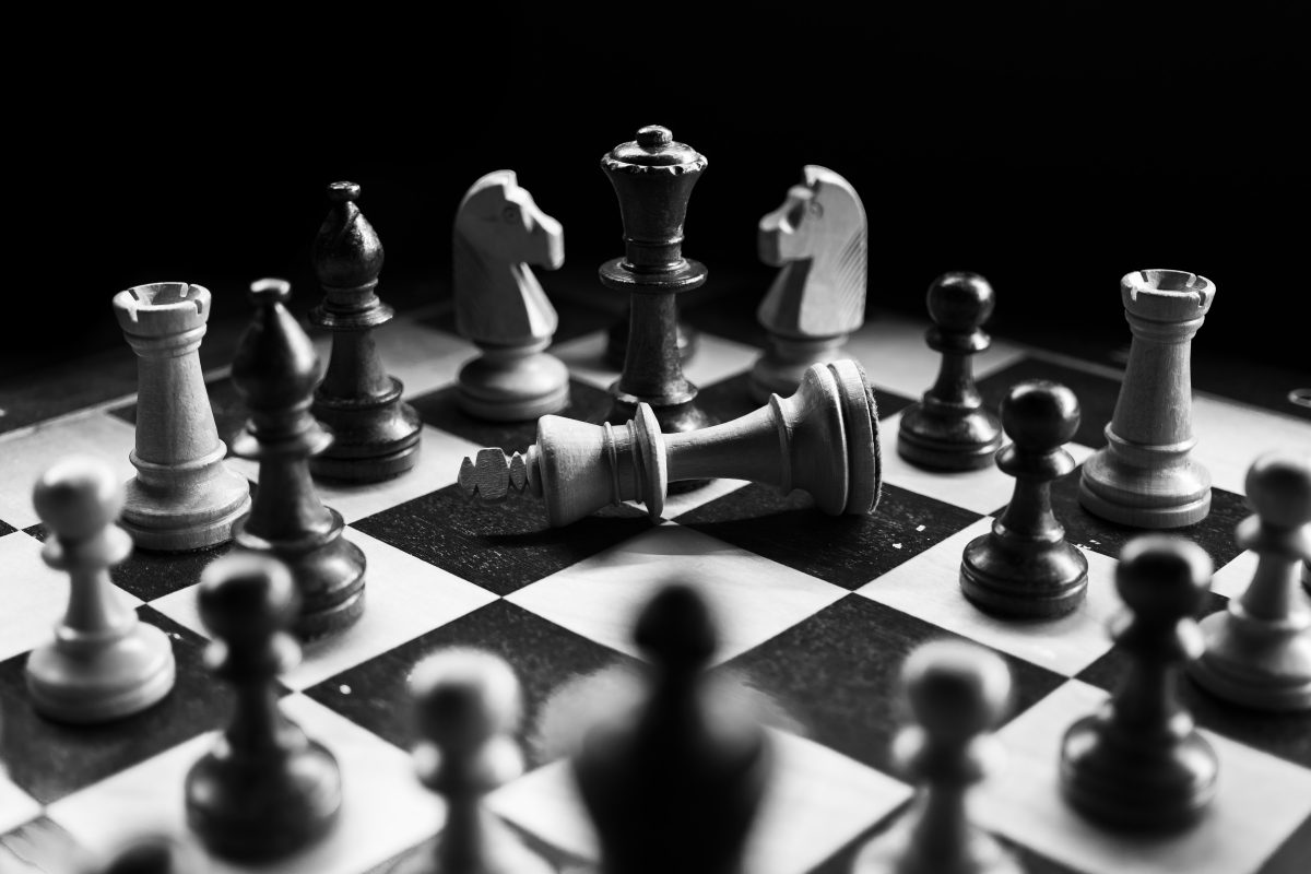Chess pieces on a board with a fallen King