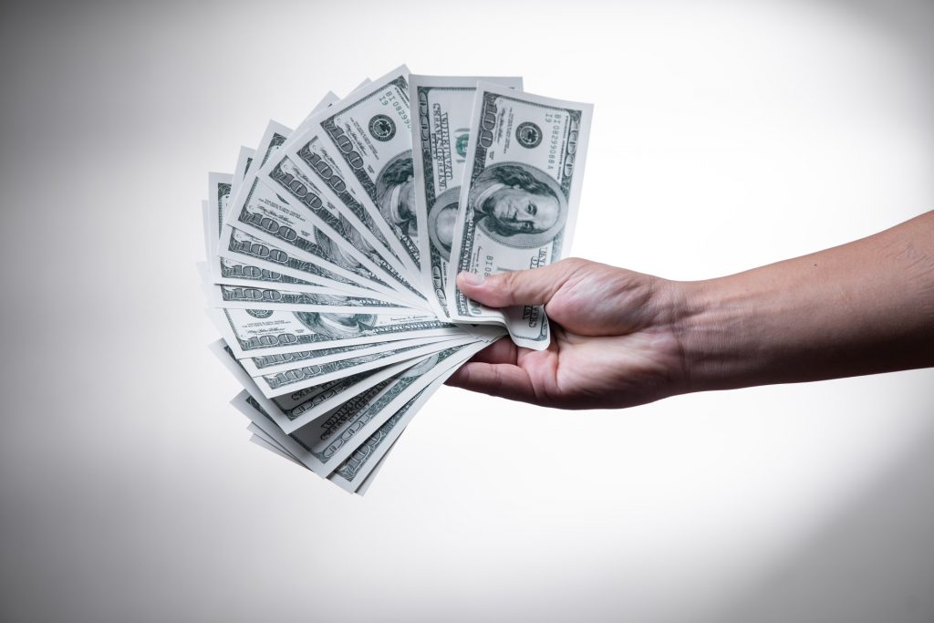 A hand holding a fanned out bunch of $100 bills