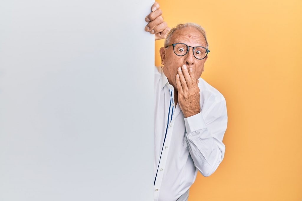 A grey-haired man in glasses peering around a corner with his hand to his mouth in a look of surprise