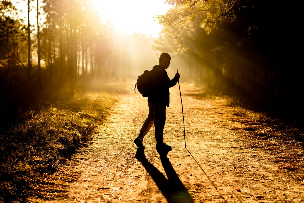 Man walking into the sunrise with a backpack and walking stick.